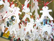 Dozens of paper cut out people with messages written on them
