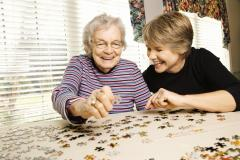 Woman helping an older woman do a jigsaw puzzle