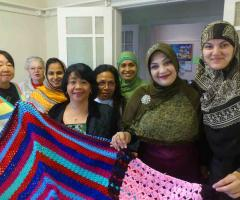 Group of women from different cultural backgrounds and different ages holding up crocheted rugs