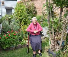 Elderly woman sitting on her walker in her garden