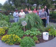 Lakemba Community Gardeners standing near the herb spiral that they built