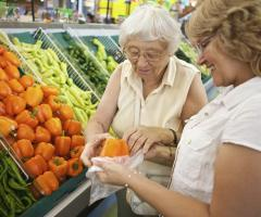 Volunteer helping elderly women with her fruit and veg shopping