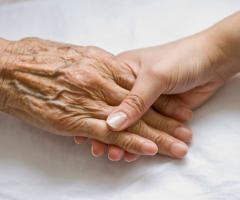 An elderly woman's hand being held by a young persons hand