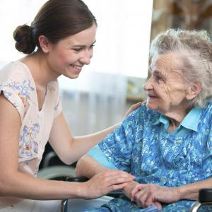 Female volunteer visiting a elderly woman in her home