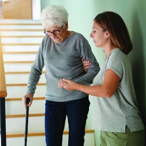 Carer helps senior woman down stairs