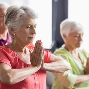 Two women and a man over 65 doing Yoga