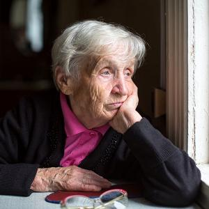 Elderly woman feeling sad as she looks out the window