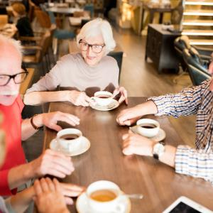 A group of senior men and women enjoying a chat over tea and coffee