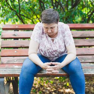A mature aged woman sitting alone and looking down on a park bench