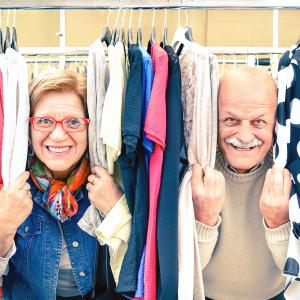 Happy senior couple smiling through clothing rack