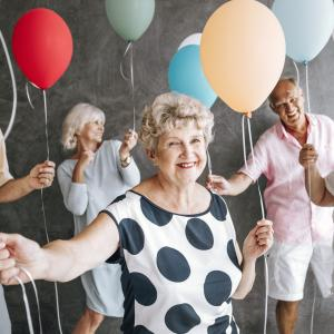 a group of men and women over 65 smiling and holding colourful balloons