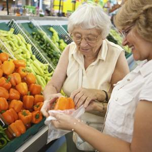 Volunteer helping elderly women with her fruit and veg shopping