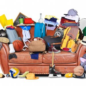 Lounge covered with clothes, sporting equipment and mess
